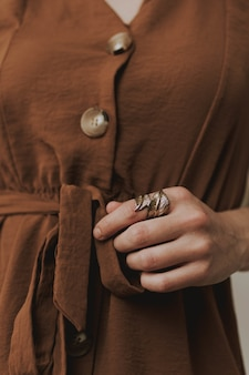 茶色のドレスと金属の葉の形をしたリングを身に着けている女性の垂直クローズアップショット
