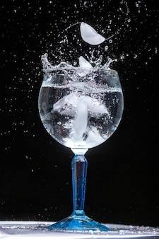 水しぶきと氷の水のガラスの垂直クローズアップショット