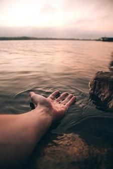 水で彼の手を持つ人の垂直のクローズアップショット