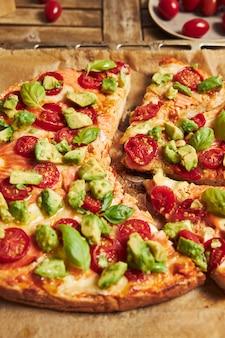 나무 테이블에 야채와 함께 피자의 수직 근접 촬영 샷