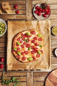 木製のテーブルに野菜とピザの垂直クローズアップショット