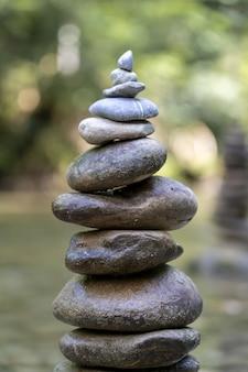 川の水の上でバランスの取れた石のピラミッドの垂直クローズアップショット