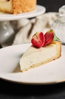 白いプレート上のイチゴのチーズケーキの垂直クローズアップショット