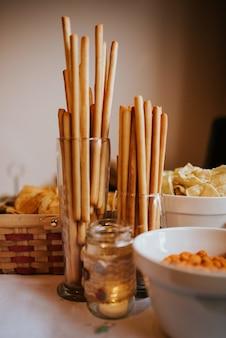 Вертикальный снимок палочек в стеклянной таре с другими закусками на столе крупным планом