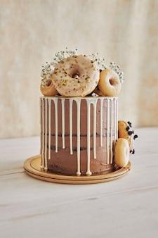 상단과 흰색 물방울에 도넛과 함께 맛있는 도넛 초코 생일 케이크의 수직 근접 촬영 샷