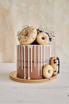 Вертикальный снимок вкусного шоколадного торта на день рождения с пончиками сверху и белой капелькой крупным планом