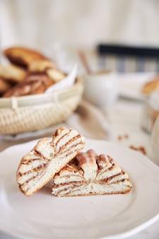 Вертикальный снимок вкусных ореховых улиток с кофе капучино на белом деревянном столе крупным планом