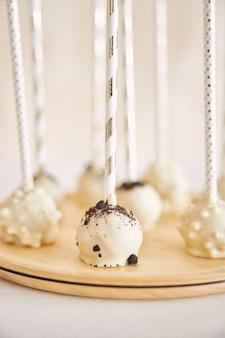白と木製のテーブルにおいしい白いケーキポップの垂直クローズアップショット