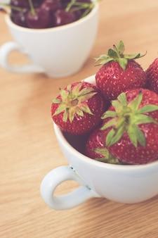 컵에 즙이 많은 딸기의 수직 근접 촬영