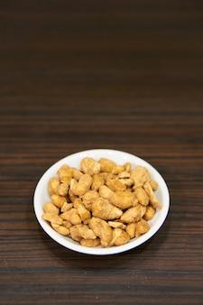Вертикальный снимок арахиса в маленькой белой миске на деревянном столе крупным планом