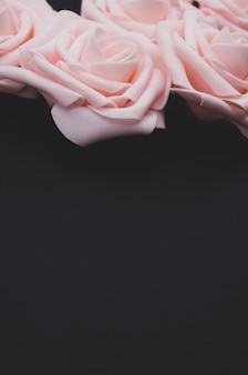 Вертикальный снимок розовых роз крупным планом на черном фоне с копией пространства