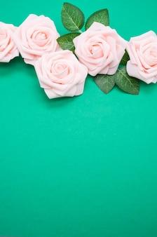 Вертикальный снимок розовых роз крупным планом на зеленом фоне с копией пространства