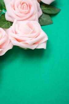 コピースペースと緑の背景に分離されたピンクのバラの垂直クローズアップショット