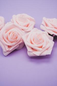 Вертикальный снимок розовых роз крупным планом на фиолетовом фоне с копией пространства