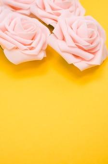 コピースペースと黄色の背景に分離されたピンクのバラの垂直クローズアップショット