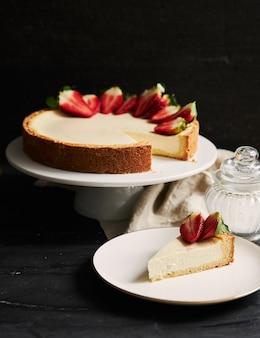 흰색 접시에 딸기 치즈 케이크의 수직 근접 촬영 샷