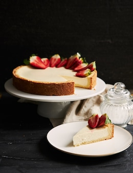 Вертикальный снимок клубничного чизкейка крупным планом на белой тарелке