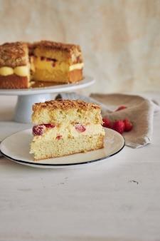하얀 탁자에 딸기를 넣은 맛있는 바닐라 크림 케이크의 수직 클로즈업 샷