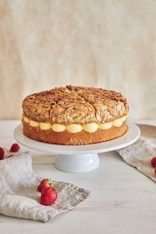 하얀 테이블에 딸기가 들어 있는 맛있는 바닐라 크림 케이크의 수직 클로즈업 샷