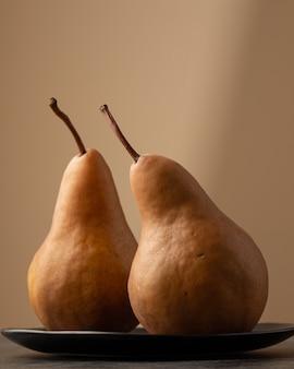 背景をぼかした写真のプレートに2つの梨の垂直のクローズアップショット