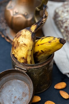 Vertical closeup shot of old bananas in a rusty can