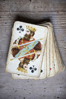 Vertical closeup shot of old weathered playing cards on a wooden table