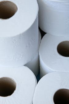 Vertical closeup shot of a pills of rolls of toilet paper