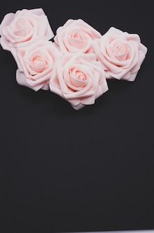Colpo verticale del primo piano di rose rosa isolato su uno sfondo nero con spazio di copia