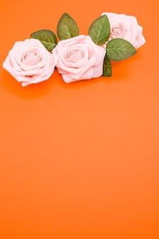 Colpo verticale del primo piano di rose rosa isolato su priorità bassa arancione con lo spazio della copia