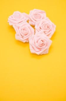 Colpo verticale del primo piano di rose rosa isolato su uno sfondo giallo con spazio di copia