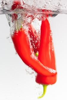 Colpo verticale del primo piano dei peperoni rossi di tabasco nell'acqua su un bianco