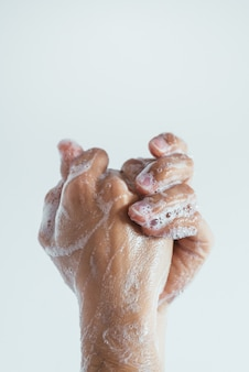Vertical closeup shot of the soaped hands of a person