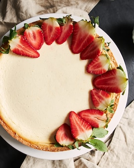 Vertical closeup shot of a strawberry cheesecake on a white plate