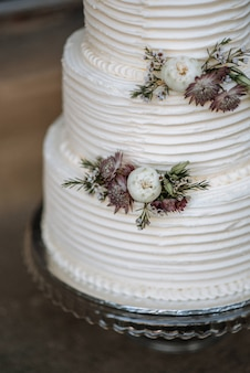 Vertical closeup shot of a three-layer wedding cake decorated with flowers on a silver platter