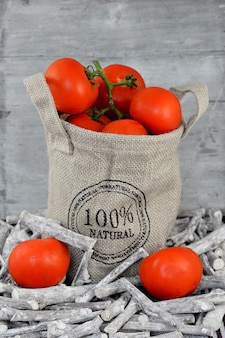 Vertical closeup shot of tomatoes in a burlap sack in twigs in front of a wooden wall