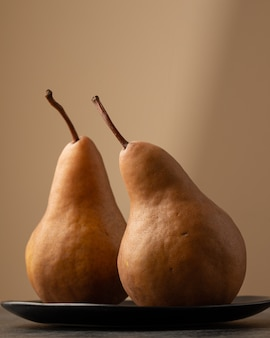 Vertical closeup shot of two pears in a plate with a blurred background
