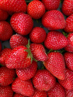 Vertical closeup shot of vibrant red juicy fresh strawberries