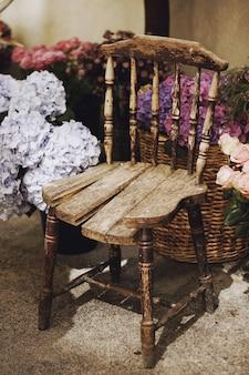 Colpo verticale del primo piano di una sedia di legno dell'annata circondata da cesti con fiori