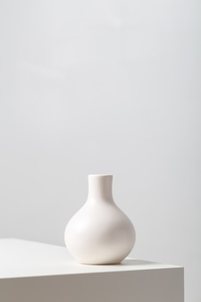 Vertical closeup of a white clay vase on the table under the lights against a white background