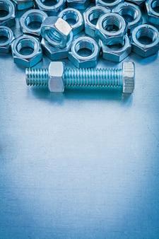 Вертикальное изображение copyspace гаек и болтов на металлической концепции конструкции предпосылки