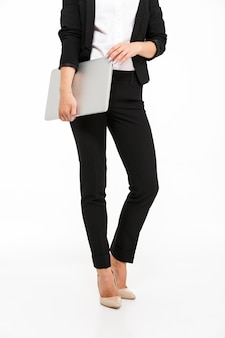 Vertical cropped image of body of business woman holding laptop computer over white wall