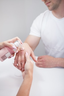 Vertical cropped shot of unrecognizable man having hand cream applied after getting manicure done at nail salon
