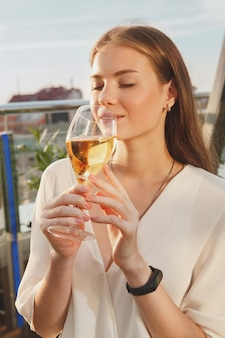 Vertical cropped shot woman smelling delicious wine outdoors