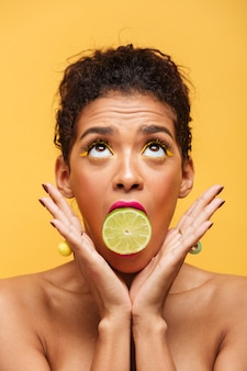 Вертикальная милая афроамериканская женщина с модным макияжем, держащая половину свежего лайма во рту, изолирована над желтой стеной