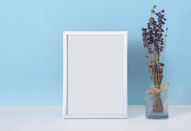 Vertical emply spring white photo frame mockup on a blue background with lavender flowers in a vase. women's day concept.