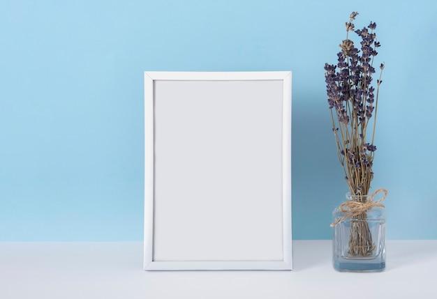 꽃병에 라벤더 꽃과 파란색 배경에 수직 emply 봄 흰색 사진 프레임 모형. 여성의 날 개념.