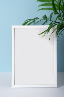 Vertical emply summer white photo frame mockup on blue background with palm leaves for your design, advertising.
