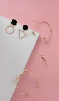 Вертикальная плоская укладка современных золотых женских аксессуаров на розово-белой угловой поверхности