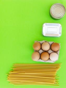 パントリーステープル付きの垂直フラットレイ。パスタ、卵、缶詰。緑の背景に基本的な製品の上面図