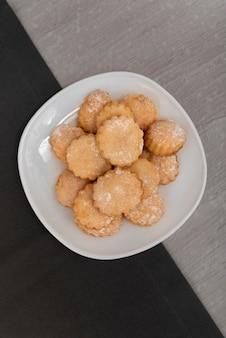 Вертикальная рамка. аппетитное песочное печенье на белой тарелке. домашнее песочное печенье. вид сверху